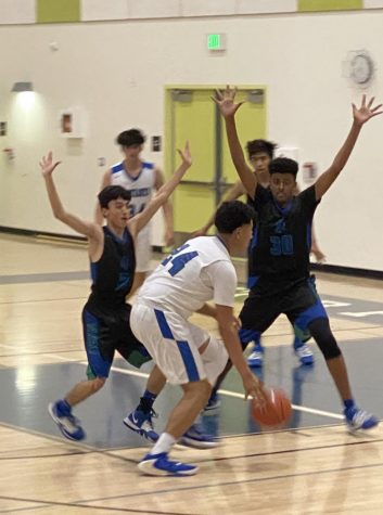 image by Stefany Silva; Three players from RFK look to guard Maywood player Damien Olmos.