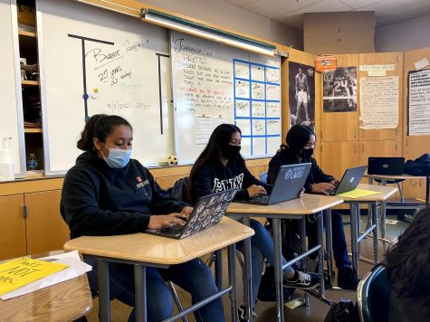 Maywood Academy High Schoolers Laysha Garcia, Casandra Mercado, Shecid Gonzales, work on their assignments to turn them in before the report card.